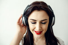 Happy pretty smiling woman with red lips listens to music in headphones Stock Photo