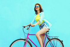 Happy pretty smiling woman rides a bicycle over colorful blue background Royalty Free Stock Photo
