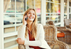 Happy pretty smiling woman talking on smartphone. In cafe Stock Photos