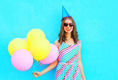 Happy pretty smiling young woman in a birthday cap with an air colorful balloons over blue background Stock Photography