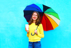 Happy pretty smiling young woman with coffee cup and colorful umbrella in autumn day over colorful blue background Royalty Free Stock Image
