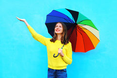 Happy pretty smiling young woman with colorful umbrella in autumn day looking up over colorful blue background Stock Photos