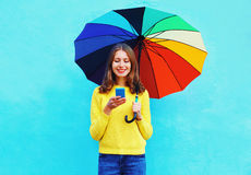 Happy pretty smiling young woman with colorful umbrella using smartphone in autumn day over colorful blue background Stock Image