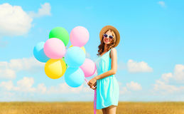 Happy pretty smiling young woman holds an air colorful balloons enjoying a summer day on a meadow blue sky. Happy pretty smiling young woman holds an air Royalty Free Stock Photos