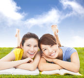 Happy pretty students lying on the grassland with books. On with blue sky Royalty Free Stock Images