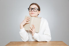 Happy pretty teenage girl in glasses sitting and holding book Stock Photo