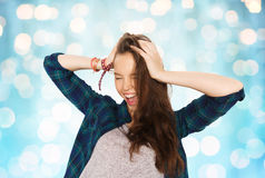 Happy pretty teenage girl holding to head. People, hair care, style and teens concept - happy pretty teenage girl holding to head over blue holidays lights Stock Image