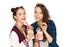 Happy pretty teenage girls drinking milk shakes. People, friends, teens and friendship concept - happy smiling pretty teenage girls drinking milk shakes and with Stock Image