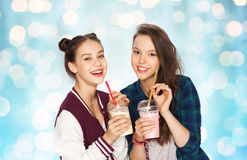 Happy pretty teenage girls drinking milk shakes. People, friends, teens and friendship concept - happy smiling pretty teenage girls drinking milk shakes and with Royalty Free Stock Image