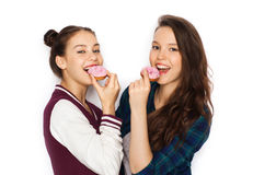 Happy pretty teenage girls eating donuts Royalty Free Stock Image