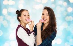 Happy pretty teenage girls eating donuts Royalty Free Stock Photo