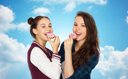 Happy pretty teenage girls eating donuts Royalty Free Stock Images