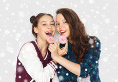Happy pretty teenage girls eating donuts Royalty Free Stock Photography