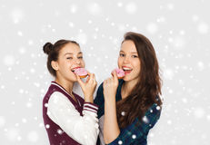 Happy pretty teenage girls eating donuts. Winter, christmas, people, holidays and fast food concept - happy smiling pretty teenage girls or friends with donuts Stock Image