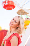 Happy pretty woman in front of a Ferris wheel Royalty Free Stock Photos