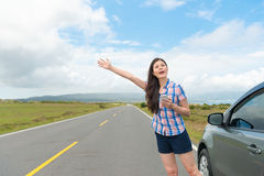 Pretty woman with hand up calling passing car. Happy pretty woman with hand up calling passing car on countryside street, using mobile phone app technology for Royalty Free Stock Images