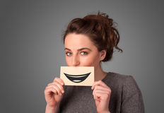 Happy pretty woman holding card with funny smiley Stock Photos