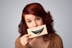 Happy pretty woman holding card with funny smiley. On gradient background Royalty Free Stock Photo