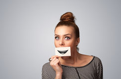 Happy pretty woman holding card with funny smiley Stock Photography