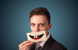 Happy pretty woman holding card with funny smiley Royalty Free Stock Images