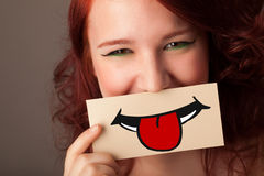 Happy pretty woman holding card with funny smiley. On gradient background Stock Images