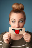 Happy pretty woman holding card with funny smiley. On gradient background Royalty Free Stock Images
