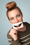 Happy pretty woman holding card with funny smiley. On gradient background Stock Photography