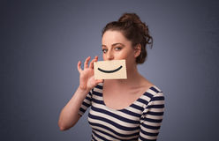 Happy pretty woman holding card with funny smiley Stock Images