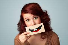 Happy pretty woman holding card with funny smiley Stock Image