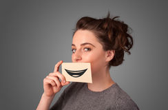 Happy pretty woman holding card with funny smiley. On gradient background Stock Image