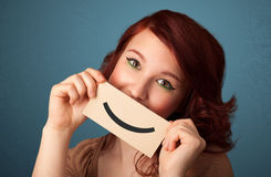 Happy pretty woman holding card with funny smiley. On gradient background Stock Photos