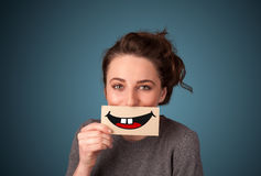 Happy pretty woman holding card with funny smiley. On gradient background Stock Photo
