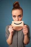 Happy pretty woman holding card with funny smiley. On gradient background Royalty Free Stock Image