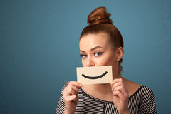 Happy pretty woman holding card with funny smiley. On gradient background Royalty Free Stock Photography