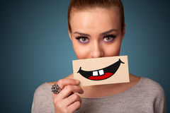Happy pretty woman holding card with funny smiley. On gradient background Royalty Free Stock Photos