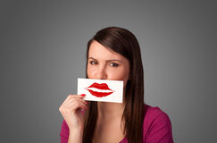 Happy pretty woman holding card with kiss lipstick mark. On gradient background Royalty Free Stock Image