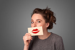 Happy pretty woman holding card with kiss lipstick mark. On gradient background Stock Image