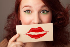 Happy pretty woman holding card with kiss lipstick mark. On gradient background Stock Photo