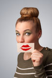 Happy pretty woman holding card with kiss lipstick mark. On gradient background Stock Photos