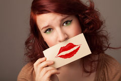 Happy pretty woman holding card with kiss lipstick mark Stock Image
