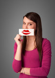 Happy pretty woman holding card with kiss lipstick mark. On gradient background Stock Photography