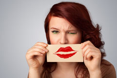 Happy pretty woman holding card with kiss lipstick mark. On gradient background Royalty Free Stock Images