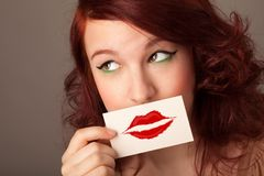 Happy pretty woman holding card with kiss lipstick mark. On gradient background Royalty Free Stock Photo