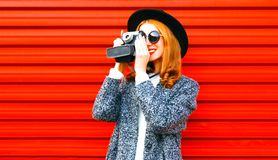 Happy pretty woman holds retro camera on red background Stock Photo