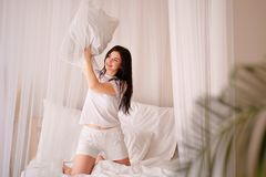 Happy pretty woman jumping on bed holding pillow royalty free stock photo
