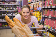 Happy pretty woman pushing trolley Royalty Free Stock Image