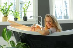 Happy pretty woman is relaxing in bath stock images