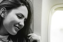 Happy pretty woman sitting in airplane next to window - Young happy girl traveling to top destinations stock images