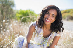 Happy pretty woman sitting on the grass in floral dress Royalty Free Stock Photo