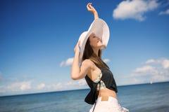 Happy pretty woman standing on beach raising hand Stock Photo